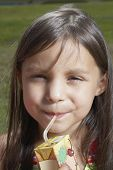 Young girl drinking out of a juice box