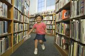 Girl running down aisle of library