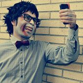 a scary hipster zombie taking a selfie of himself with a smartphone, with a retro effect