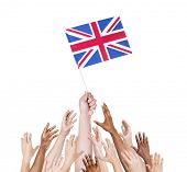 Group of multi-ethnic people reaching for and holding the flag of United Kingdom.