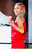 Asian woman drinking cocktails in fancy bar or club