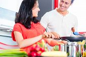 Woman and man cooking meat in domestic kitchen