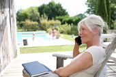 Senior woman on the phone by swimming-pool