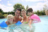 stock photo of swimming pool family  - Happy family enjoying swimming time in pool - JPG