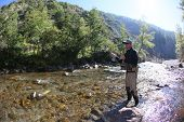 foto of fly rod  - Fly fisherman using flyfishing rod in beautiful river  - JPG