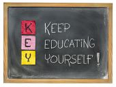 KEY acronym - keep educating yourself - sticky notes and chalk writing on a blackboard