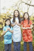 Three young Asian sisters holding fortune cookies