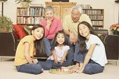 foto of chinese checkers  - Three young Asian sisters playing chinese checkers while grandparents watch - JPG