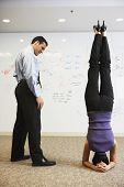 Businesswoman doing headstand next to businessman in front of whiteboard wall