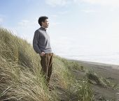 Asian man standing on the dunes