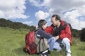 Asian father and son with backpacks outdoors