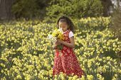 Young Hispanic girl smelling picked flowers outdoors