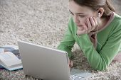 Young girl lying on the floor with laptop