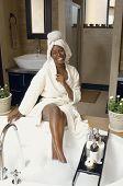 African American woman in bathrobe drawing a bath