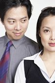 Close up of Asian businessman looking at Asian businesswoman