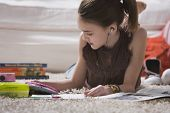 picture of pre-adolescent girl  - Young girl with headset doing homework on floor - JPG