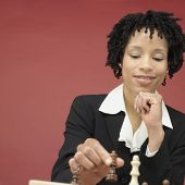 Studio shot of African woman playing chess