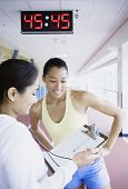 Female runner reviewing time on indoor track