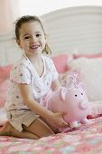 Young girl with piggy bank on bed