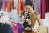 Asian woman looking holding up shirt at boutique