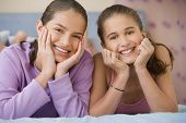 picture of laying-in-bed  - Hispanic sisters laying on bed smiling - JPG