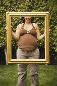 Pregnant woman holding up picture frame outdoors