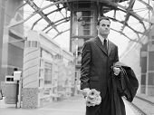 Man holding flowers and waiting at train station
