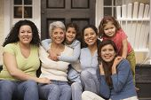 stock photo of niece  - Female Hispanic family members sitting on the porch smiling - JPG