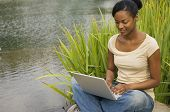 African woman sitting next to still water using laptop
