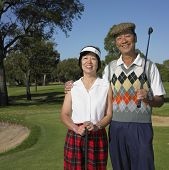Senior Asian couple smiling on golf course