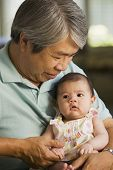 Asian grandfather holding baby granddaughter