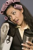 Hispanic businesswoman with curlers in hair holding coffee mug and newspaper and using cell phone