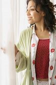 African woman in pajamas looking out window