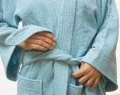 Close up of woman tying bathrobe