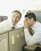 Two businessmen whispering over cubicle wall