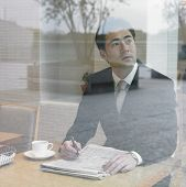 Asian businessman with paperwork looking out window