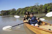 Hispanic mother and son paddling canoe