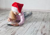 Child in christmas hat with tablet lying on floor. Girl playing computer