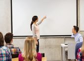 education, high school, technology and people concept - smiling student girl standing in front of white board and teacher with laptop computer in classroom