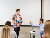 education, high school, technology and people concept - smiling student boy with notebook, laptop computer standing in front of students and teacher showing thumbs up gesture in classroom