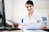 Beautiful business woman looking at papers
