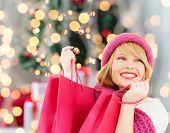 happiness, winter holidays and people concept - smiling young woman in hat and scarf with pink shopping bags over christmas tree background