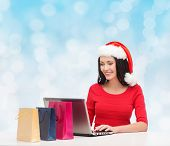 christmas, holidays, technology and people concept - smiling woman in santa helper hat with shopping bags and laptop computer over blue lights background