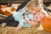 Sweet Little Boy Plays with His Baby Sister in a Rustic Ranch Setting at the Pumpkin Patch.