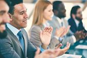 Young business partners applauding at seminar, focus on smiling man