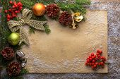 holiday decoration with paper, snow, bells, green branch and pine cones on wooden frozen table, chr