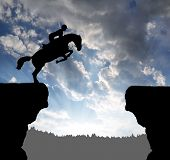 silhouette of a rider on a jumping horse