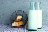 Retro bottles of tasty milk and bread, on table