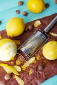 Lemons, nutmegs and grater on paper on blue wooden background