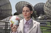 Hispanic businesswoman holding globe in front of satellite dishes